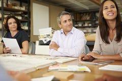坐在表附近的小组建筑师开会议 库存图片