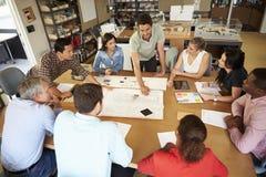 坐在表附近的小组建筑师开会议 图库摄影