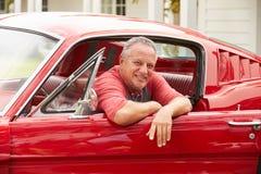 坐在被恢复的经典汽车的退休的老人 免版税库存图片