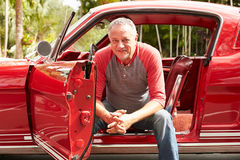 坐在被恢复的经典汽车的退休的老人 免版税库存照片