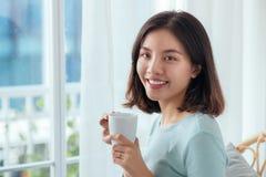 坐在被打开的窗口饮用的咖啡的年轻俏丽的妇女 库存图片