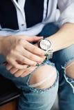 坐在被撕毁的牛仔裤和绿色现代修指甲,桥梁银手表,镯子的时髦的女孩 时尚,生活方式,秀丽,服装 免版税图库摄影