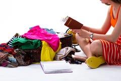 坐在被过度充填的手提箱附近的女孩 库存图片