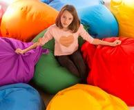 坐在装豆子小布袋椅子之间的年轻愉快的女孩 图库摄影