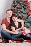 坐在装饰的新年树附近的年轻和愉快的家庭夫妇 特写镜头表面纵向妇女 免版税库存图片
