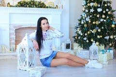 坐在装饰的白色壁炉和圣诞树附近的少妇 免版税库存照片