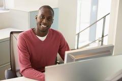 坐在计算机书桌的商人 免版税库存图片