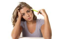 坐在计算机书桌的年轻白种人有吸引力的学生女孩或职业妇女金发蓝眼睛哀伤在看起来的重音疲乏 免版税库存图片