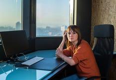 坐在计算机前面的偶然端庄的妇女在办公室窗口背景 免版税库存照片