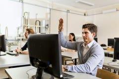 坐在计算机前面的年轻英俊的人举手 图库摄影