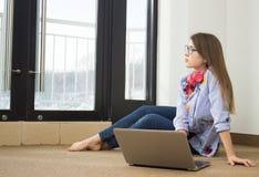 坐在计算机的女孩在窗口 库存照片