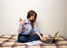 坐在计算机的女孩 免版税库存照片