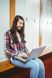 坐在计算机的微笑的学生 免版税图库摄影