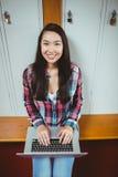 坐在计算机的微笑的学生 免版税库存图片