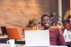 坐在计算机的非裔美国人的商人在起始的办公室 免版税图库摄影