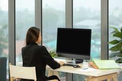 坐在计算机b前面的衣服的年轻亚裔女实业家 免版税图库摄影