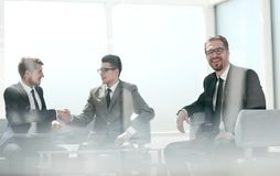 坐在谈判的选项的受欢迎的握手商人 库存图片