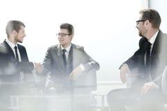 坐在谈判的选项的受欢迎的握手商人 免版税库存照片