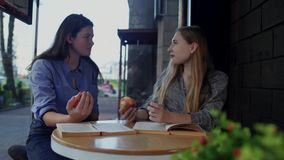 坐在谈论街道的咖啡馆的一张桌上的两个女孩吃苹果和书 女孩带领一种健康生活方式和 影视素材
