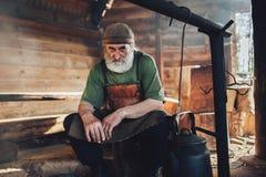 坐在谷仓的装饰胸襟的老胡子林务员 库存照片