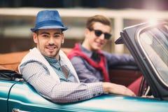 坐在豪华减速火箭的敞蓬车汽车的两时尚人 免版税图库摄影