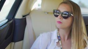 坐在豪华汽车后面的俏丽的妇女,看窗口,在头发的风 股票视频