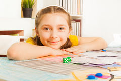 坐在赌桌上的逗人喜爱的微笑的女孩 免版税图库摄影