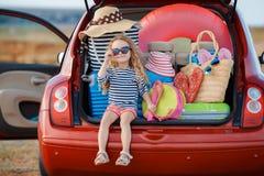 坐在车厢的愉快的女婴 免版税库存照片