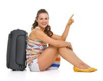 坐在轮子袋子附近的愉快的年轻旅游妇女 图库摄影