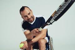 坐在轮椅和拿着网球拍和球的愉快的网球员 免版税库存照片