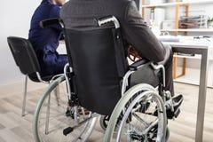 坐在轮椅的商人 免版税库存照片