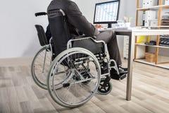 坐在轮椅的商人 免版税库存图片