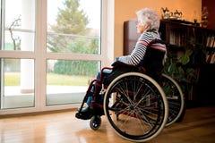 坐在轮椅的寂寞资深妇女在老人院 免版税库存图片