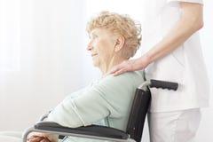 坐在轮椅的年长妇女 免版税库存照片