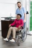 坐在轮椅的微笑的患者,当站立在的护士Ho时 库存照片