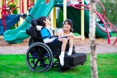 坐在轮椅的残疾兄弟旁边的姐妹在playgro 免版税库存照片
