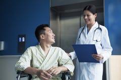 坐在轮椅的年轻微笑的男性患者,看站立在他旁边的医生 库存图片