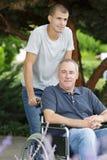坐在轮椅oudtoors的儿子和爸爸 库存照片