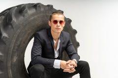 坐在轮胎的黑衣服的时髦的帅哥 免版税库存照片