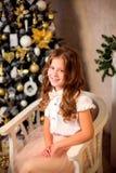 坐在软的椅子的小微笑的女孩 免版税库存照片