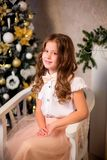 坐在软的椅子的小微笑的女孩 免版税库存图片