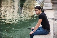坐在运河旁边的年轻人在威尼斯,意大利 库存图片