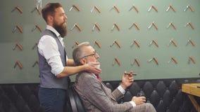 坐在选择理发设计的椅子的理发店的有胡子的老商人 股票录像