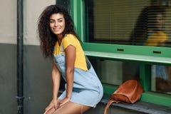 坐在都市窗口里的年轻北部非洲微笑的妇女 户外便服的阿拉伯女孩 愉快的女性佩带的黄色t- 免版税库存图片