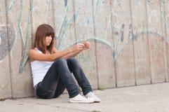 坐在都市environm的逗人喜爱的孤独的十几岁的女孩 免版税库存图片