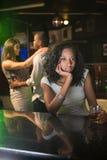 坐在酒吧柜台和夫妇跳舞的不快乐的妇女在她后 库存照片
