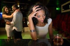 坐在酒吧柜台和夫妇跳舞的不快乐的妇女在她后 库存图片