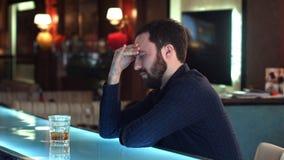 坐在酒吧柜台和拿着玻璃的沮丧的年轻人 库存图片