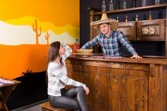 坐在酒吧柜台的一个少妇在侍酒者w旁边 免版税库存图片