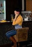 坐在酒吧柜台的时髦的妇女 免版税库存照片